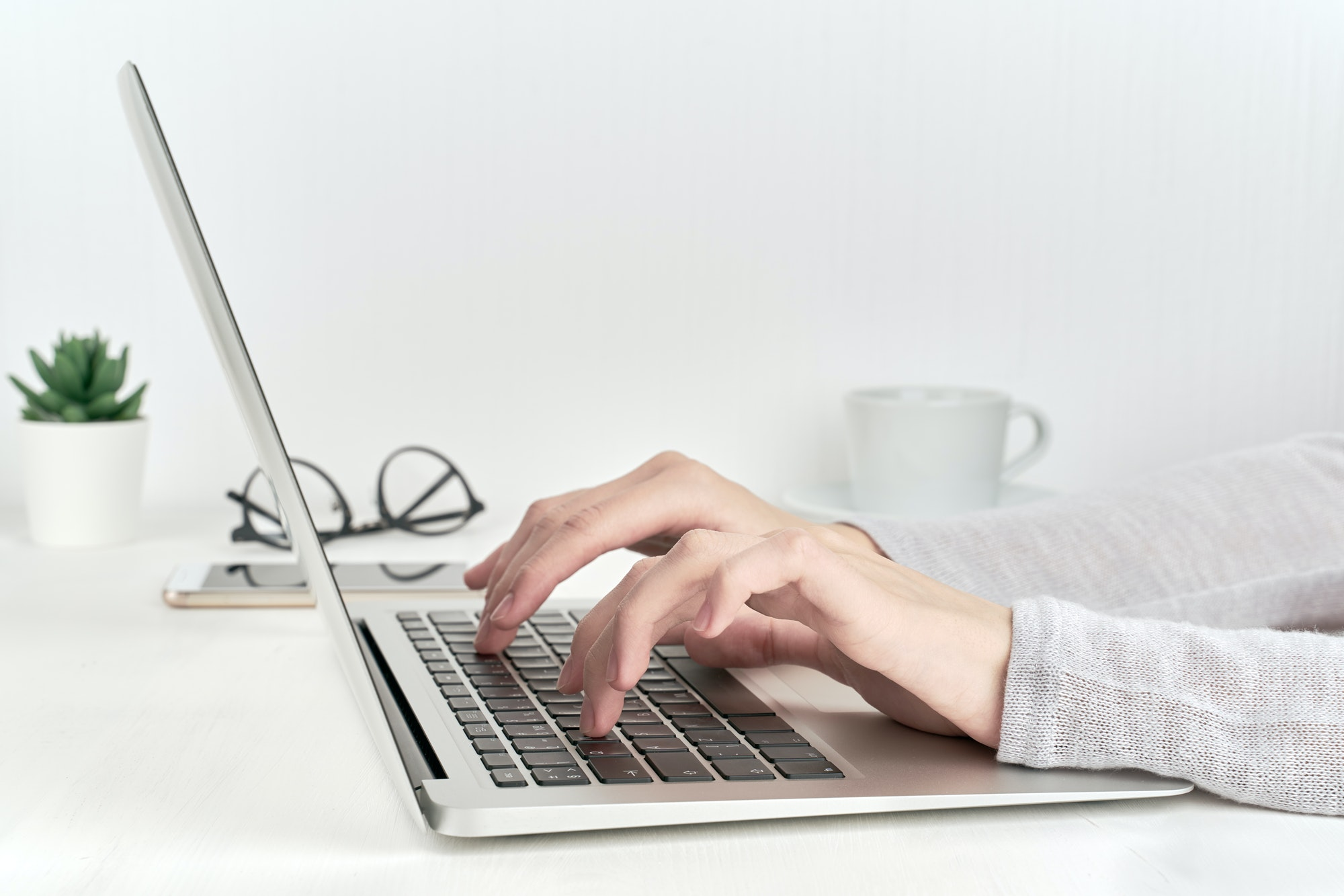 person typing on laptop keyboard, modern concept of office work or studying